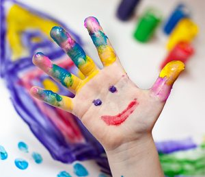 Child's hand with paint on fingers and a painted smiley face on palm