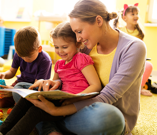 Woman reading book to child with other children playing in the background