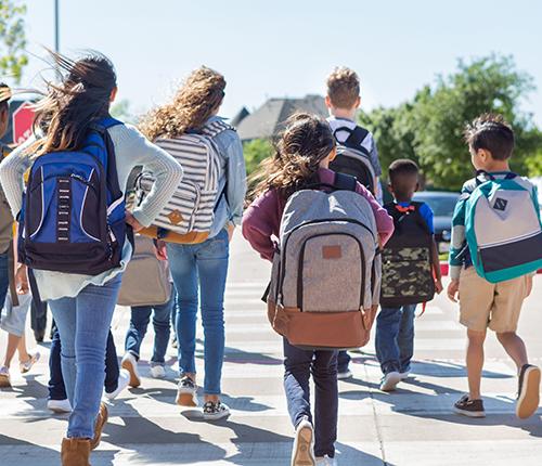 Kids wearing backpacks walking together to school